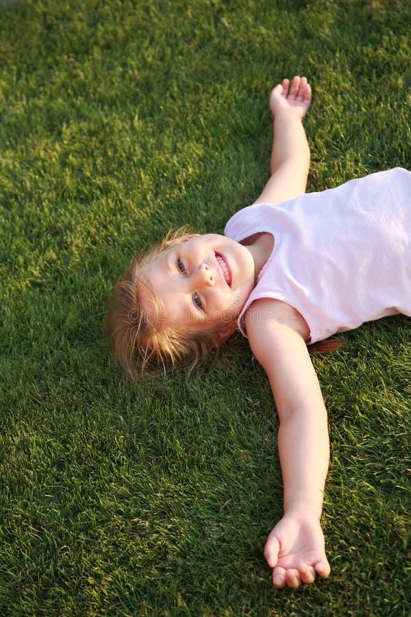 Fille heureuse détendant sur une herbe photo stock