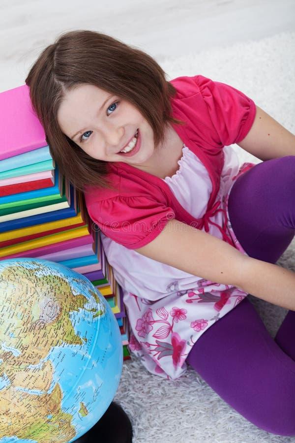Fille heureuse d'école avec les livres et le globe photos stock