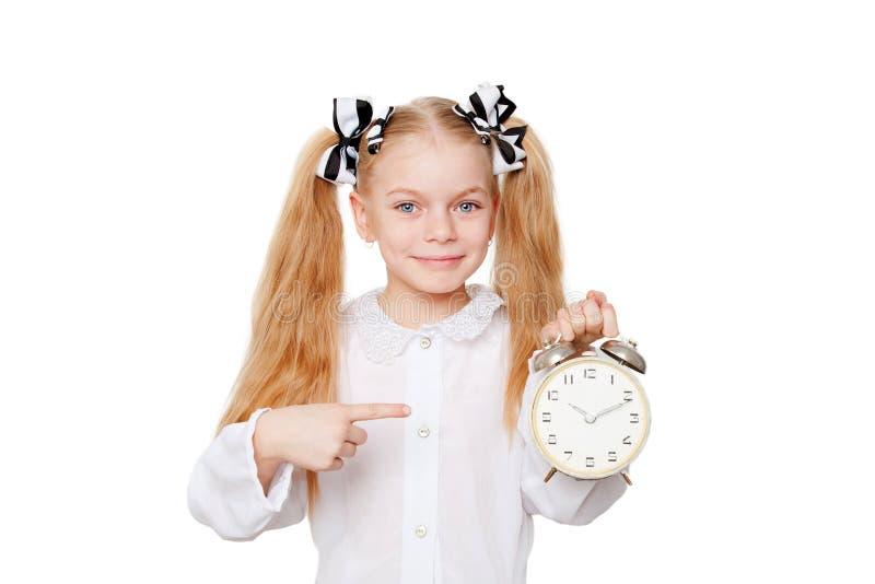 Fille heureuse d'école se dirigeant sur l'horloge photo stock