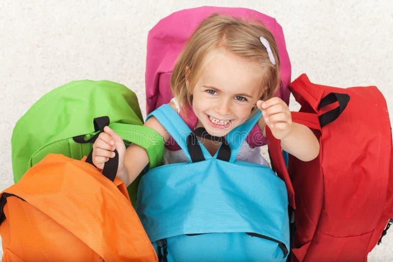 Fille heureuse d'élève du cours préparatoire choisissant son sac d'école d'un s coloré image libre de droits