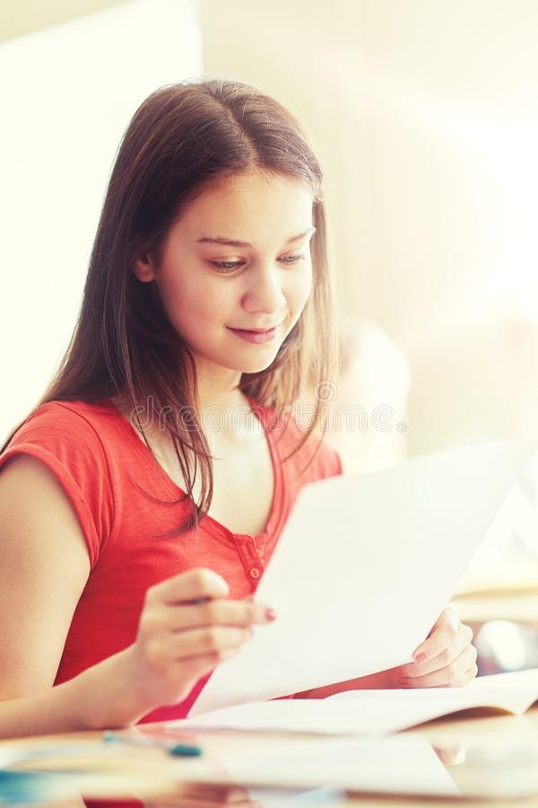 Fille heureuse d'étudiant avec le papier réactif à l'école images stock