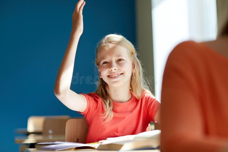 Fille heureuse d'étudiant soulevant la main à la leçon d'école photos stock