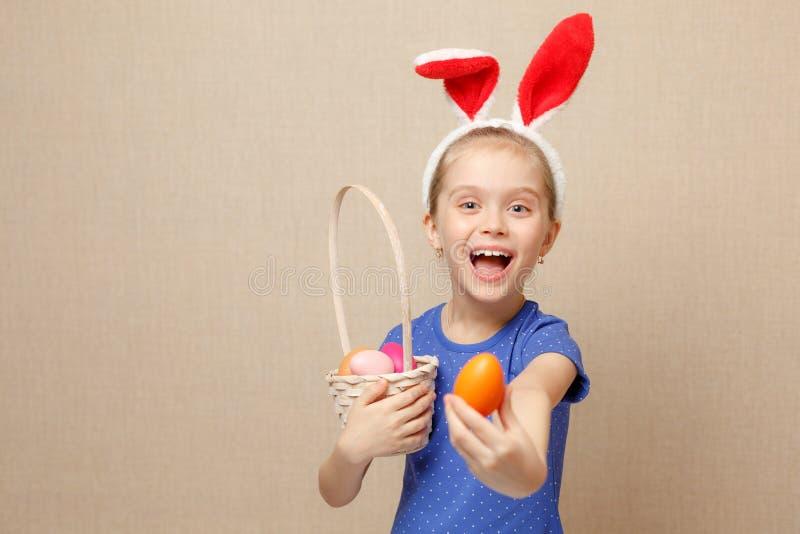 Fille heureuse d'enfant avec des oreilles de lapin et des oeufs de pâques image libre de droits