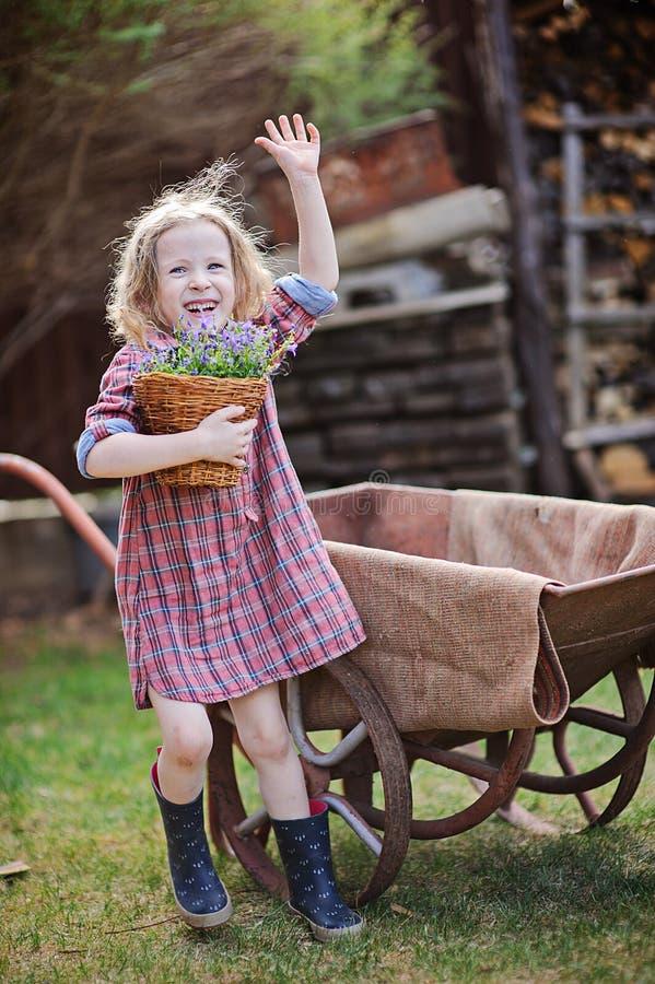 Fille heureuse d'enfant avec le jardin de jacinthes des bois au printemps près de la brouette photographie stock