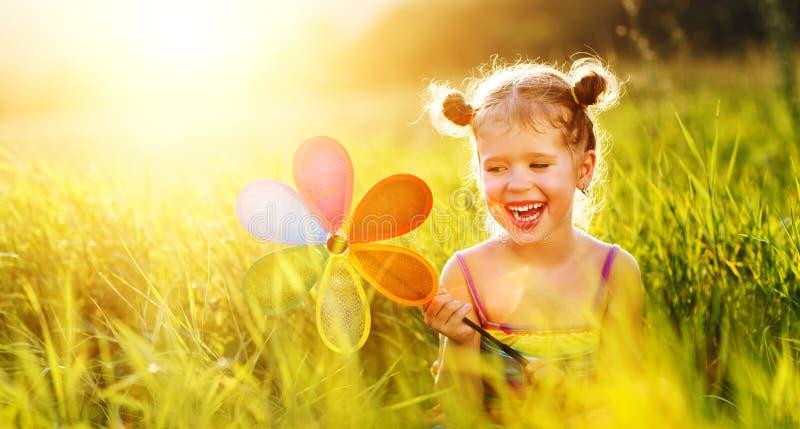Fille heureuse d'enfant avec le moulin à vent coloré de soleil en été photos stock