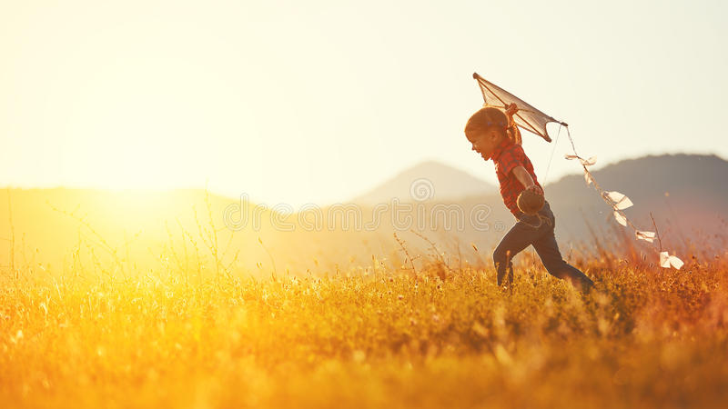 Fille heureuse d'enfant avec un cerf-volant fonctionnant sur le pré en été image stock
