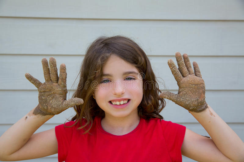 Fille heureuse d'enfant jouant avec la boue avec le sourire sale de mains photos stock