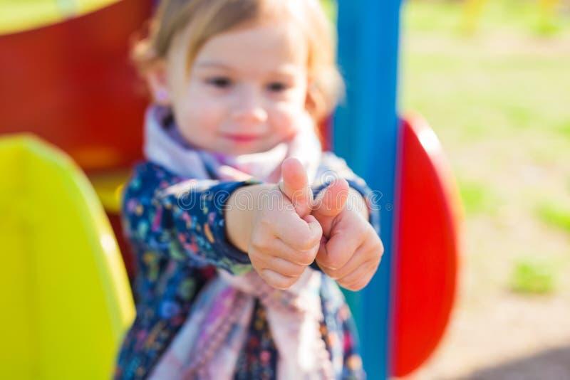 Fille heureuse d'enfant montrant des pouces  images libres de droits