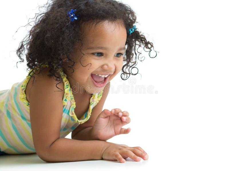 Fille heureuse d'enfant se trouvant sur le plancher et jouer d'isolement images stock