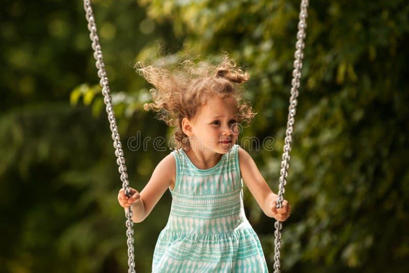 Fille heureuse d'enfant sur l'oscillation le jour chaud et ensoleillé dehors Peu enfant jouant sur la promenade de nature dans le image stock