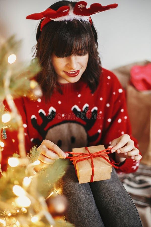 Fille heureuse dans des andouillers de renne ouvrant le boîte-cadeau au beauti d'or photo libre de droits