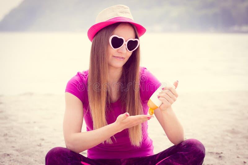 Fille heureuse dans le chapeau de paille et des lunettes de soleil utilisant la lotion du soleil, protection du soleil sur la pla photographie stock libre de droits