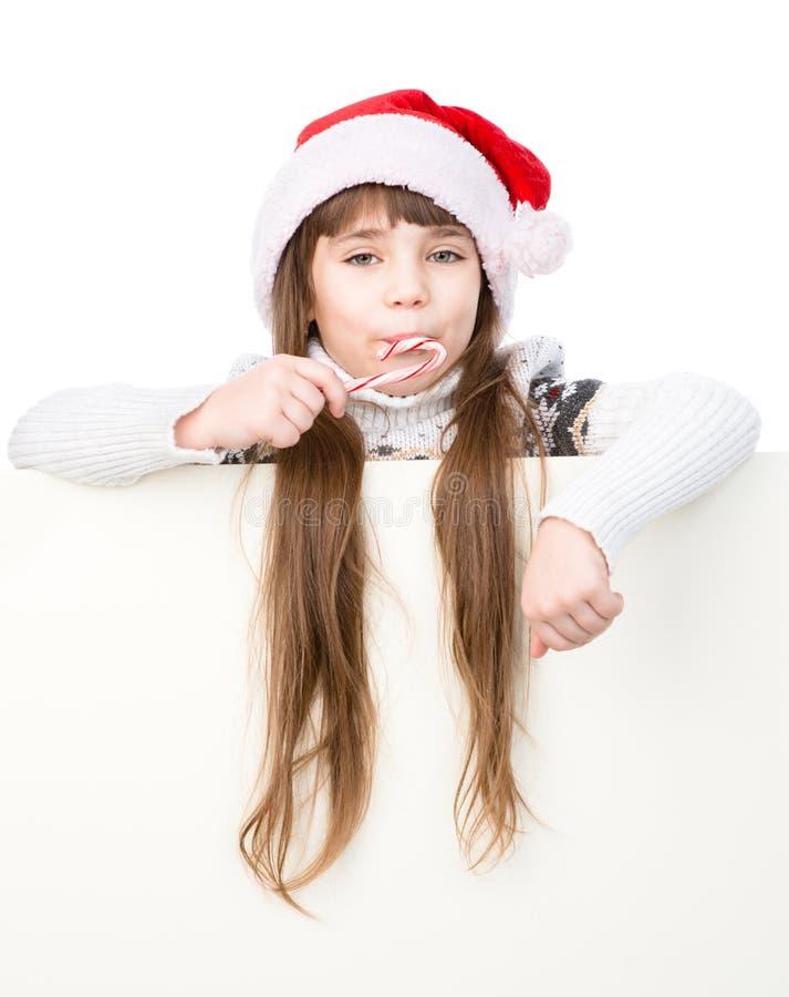Fille heureuse dans le chapeau de Santa avec le behin debout de canne de sucrerie de Noël derrière la bannière Sur le blanc image libre de droits