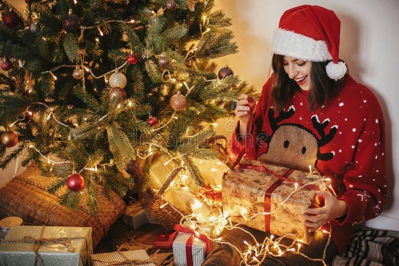 Fille heureuse dans le chapeau de Santa tenant le boîte-cadeau au beau chr d'or photos libres de droits