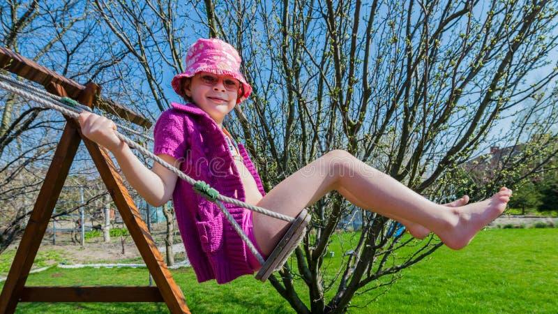 fille heureuse dans un chapeau rose ayant l'amusement sur une oscillation extérieure images libres de droits