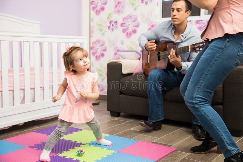 Fille heureuse dansant à sa maman et papa images libres de droits