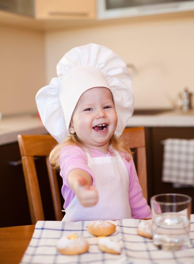 Fille heureuse de cuisinier s'asseyant à la cuisine avec des biscuits photos stock