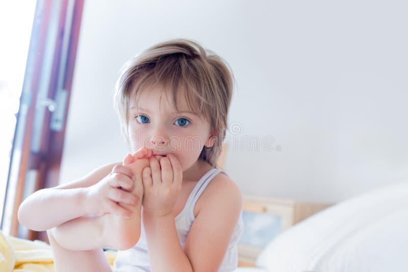 Fille heureuse de fille mangeant son pied regardant l'appareil-photo sur le lit du ` s de parent le matin Vie de famille décontra photos stock