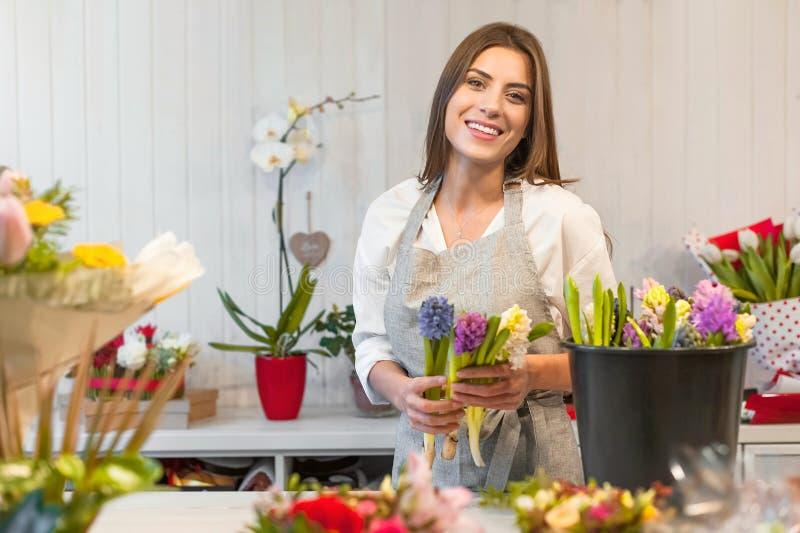 Fille heureuse de fleuriste appréciant le travail avec des fleurs photos stock
