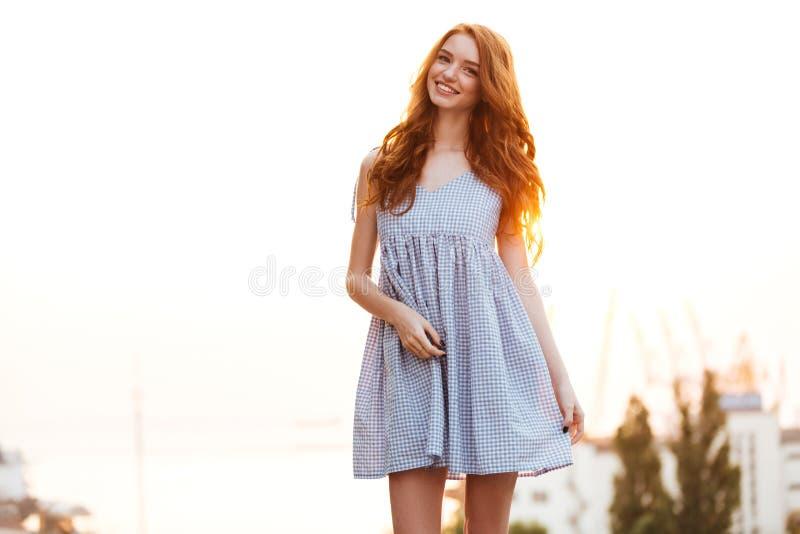 Fille heureuse de gingembre dans la robe posant sur le coucher du soleil photographie stock libre de droits