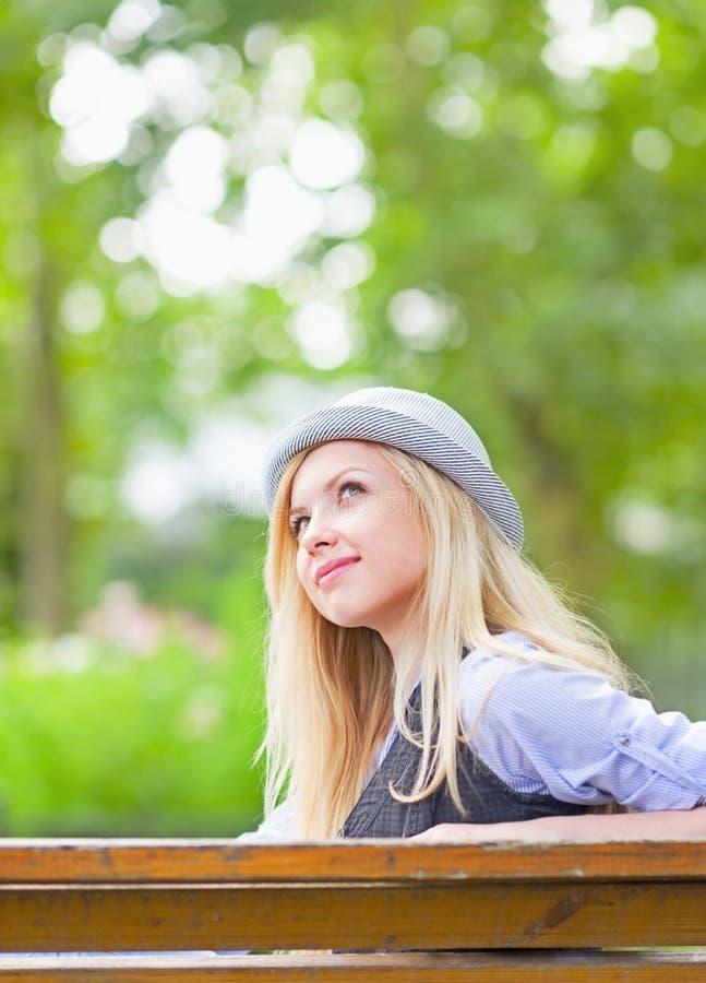 Fille heureuse de hippie dans le chapeau se reposant sur le banc en parc image libre de droits