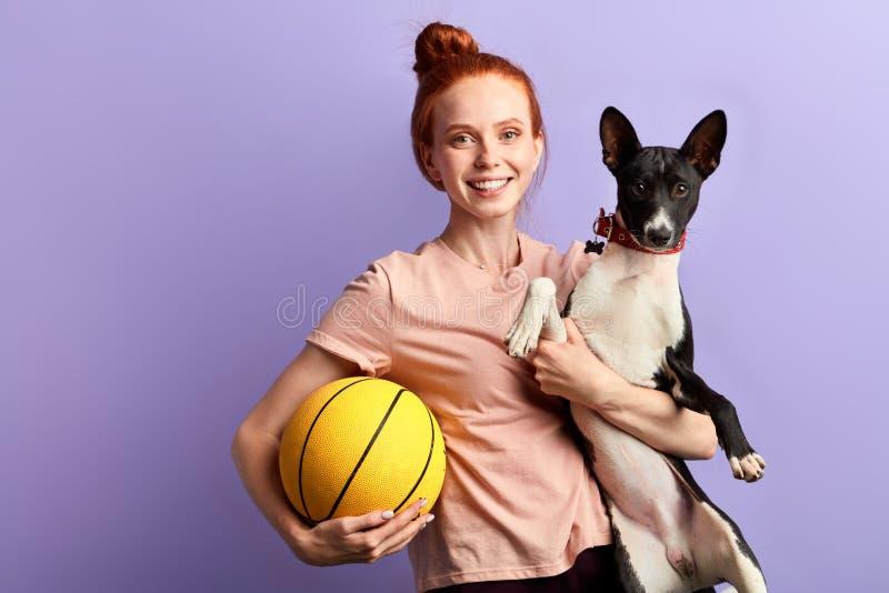 Fille heureuse de jeune gingembre jouant avec son chien image stock