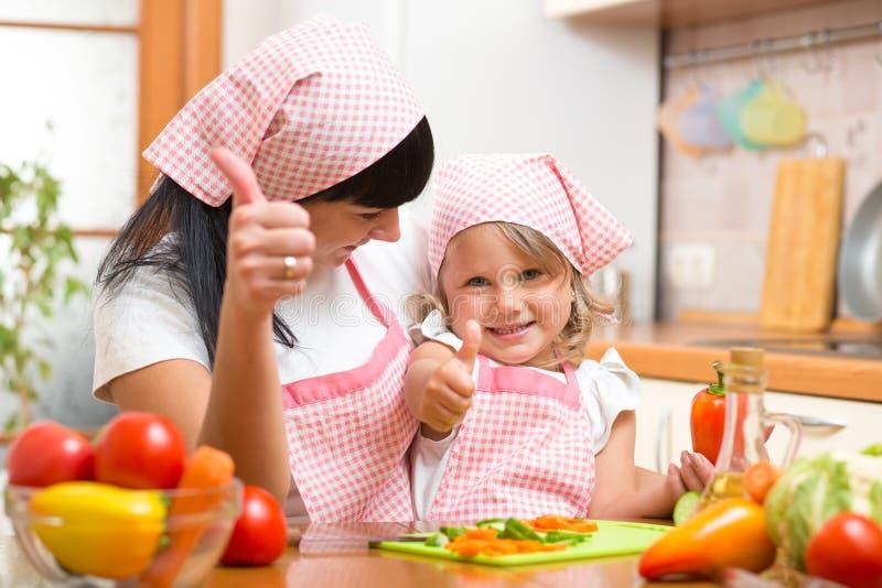 Fille heureuse de mère et d'enfant avec les légumes frais montrant des pouces  Tiré dans la cuisine image stock