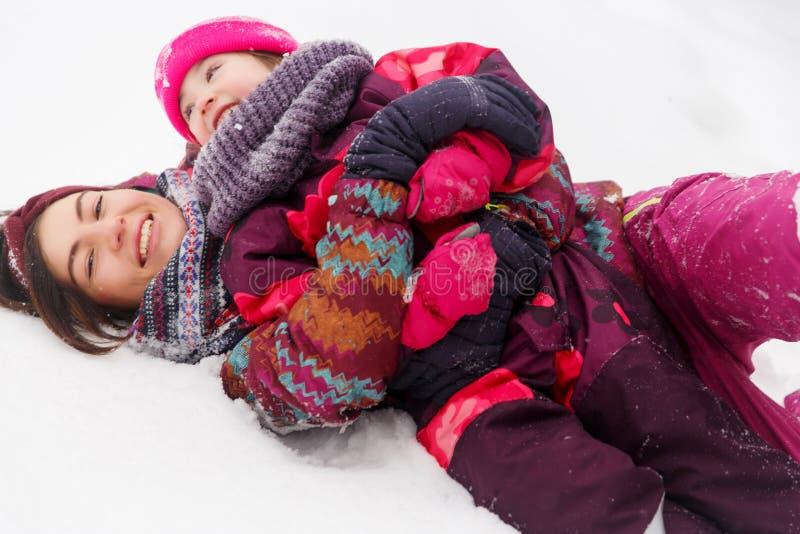 Fille heureuse de mère sur la neige photographie stock libre de droits