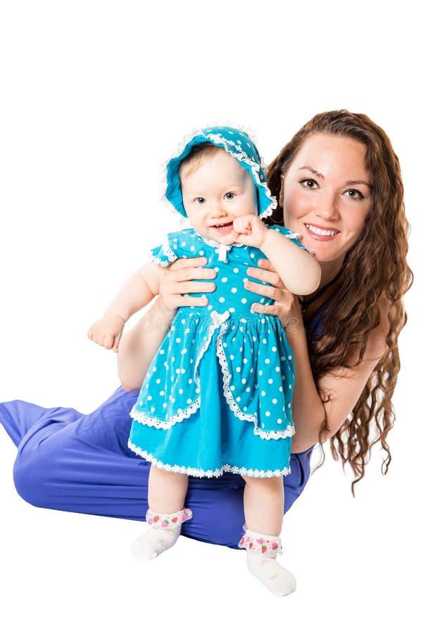 Fille heureuse de maman et d'enfant étreignant l'isolat sur le fond blanc. Le concept de l'enfance et de la famille. photographie stock libre de droits