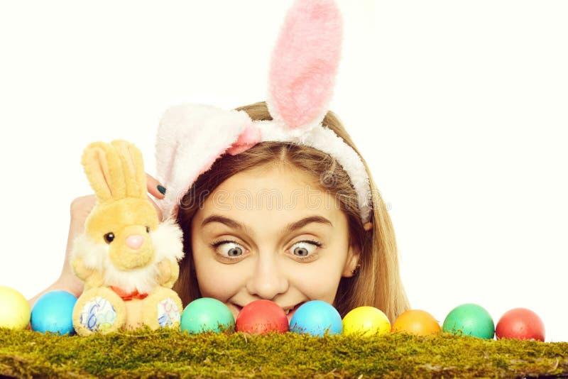 Fille heureuse de Pâques dans des oreilles de lapin avec les oeufs colorés, lapin image libre de droits
