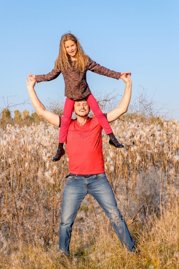 Fille heureuse de fille de père et d'enfant s'asseyant sur sa tête photographie stock libre de droits