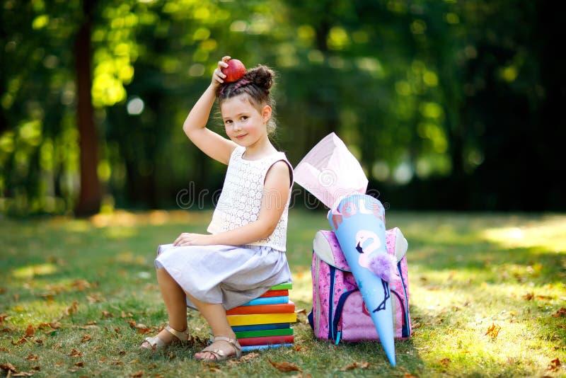 Fille heureuse de petit enfant avec le sac à dos ou la sacoche, les livres, la pomme et le grand sac ou cône d'école traditionnel photographie stock