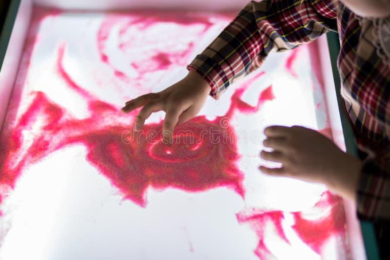Fille heureuse de petit enfant dans le dessin rouge de robe par des doigts sur l'animation rose lumineuse de sable image stock