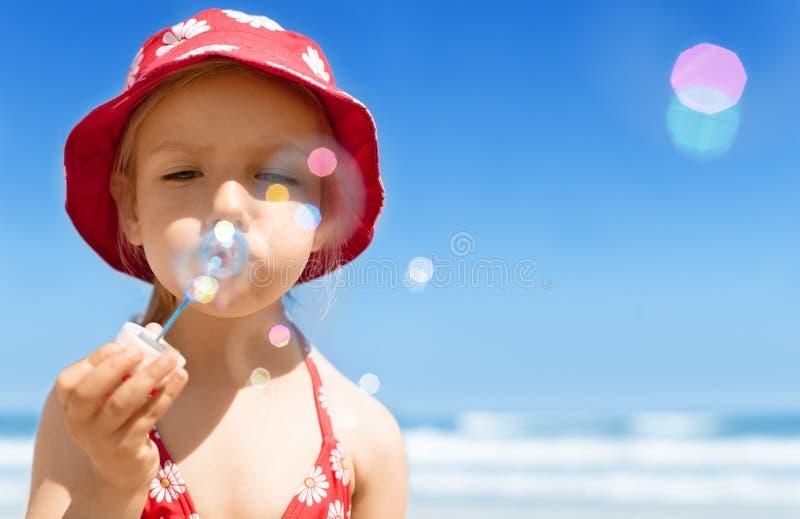 Fille heureuse de soufflement d'enfant de bulles de savon, jouant, ayant l'amusement sur la plage d'été images libres de droits