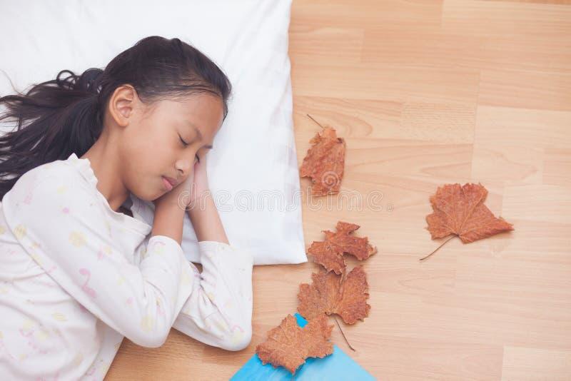 Fille heureuse dormant tout en se situant dans le salon avec d brun image libre de droits