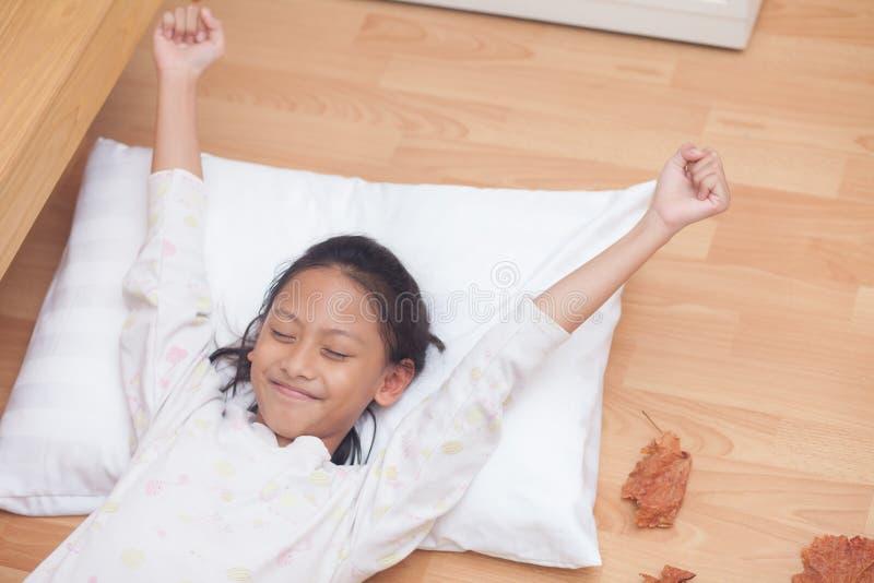 Fille heureuse dormant tout en se situant dans le salon avec d brun photographie stock libre de droits