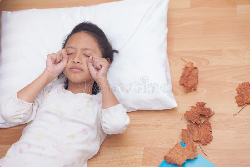 Fille heureuse dormant tout en se situant dans le salon avec d brun photographie stock