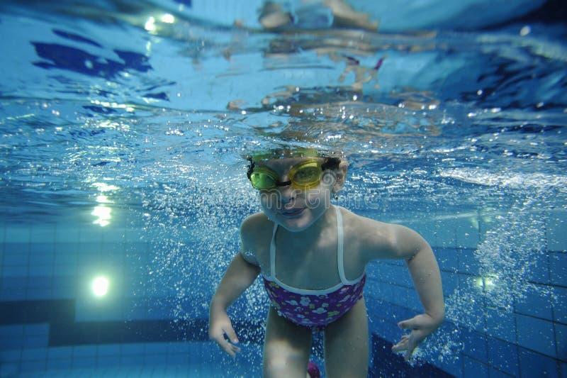Fille heureuse drôle d'enfant en bas âge nageant sous l'eau dans une piscine avec un bon nombre de bulles d'air photographie stock