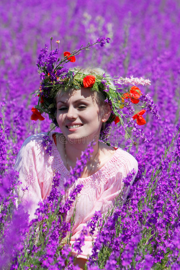 Fille heureuse en fleurs violettes photo stock