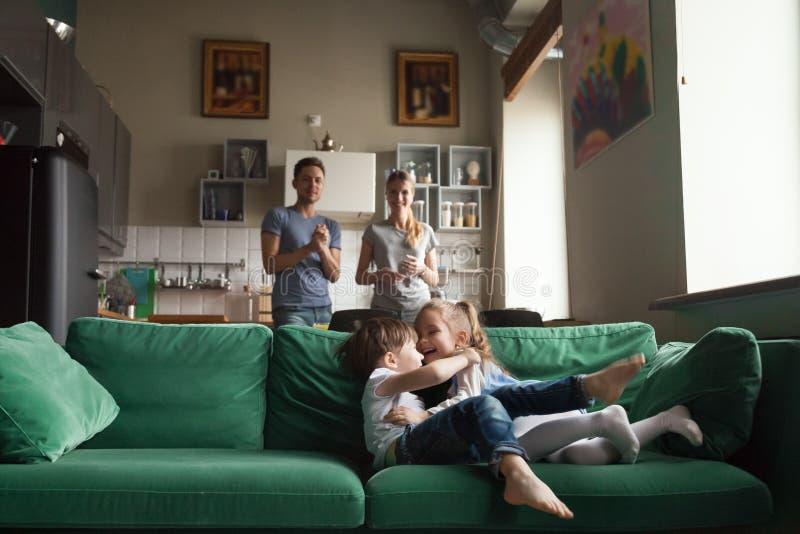 Fille heureuse et garçon préscolaires mignons jouant ensemble sur le sofa photos libres de droits