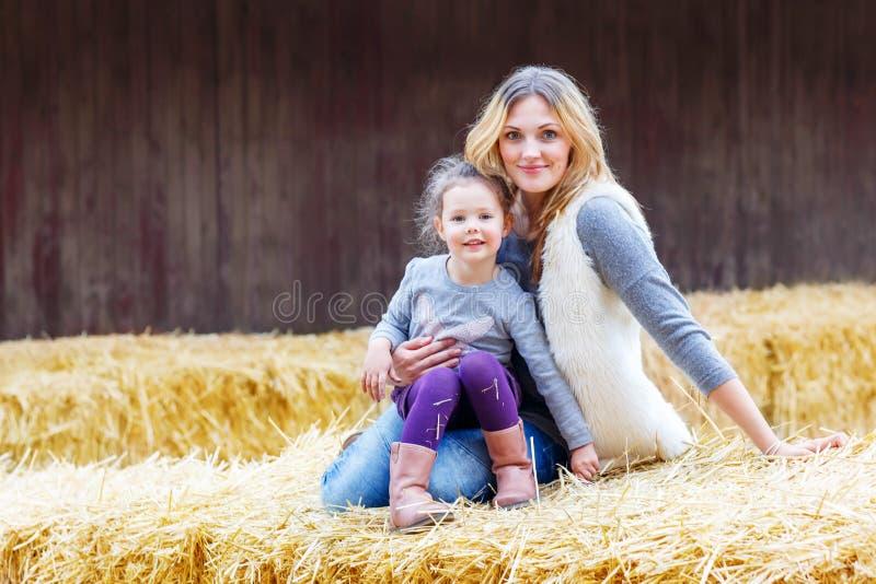 Fille heureuse et mère ayant l'amusement avec le foin à une ferme image libre de droits