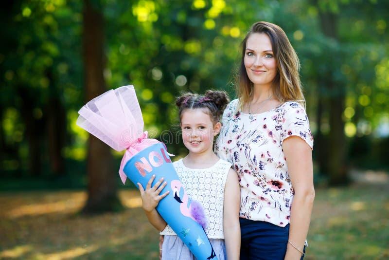 Fille heureuse et mère de petit enfant avec le grand cône traditionnel de cadeau d'école en Allemagne écolier le premier jour d'é images libres de droits