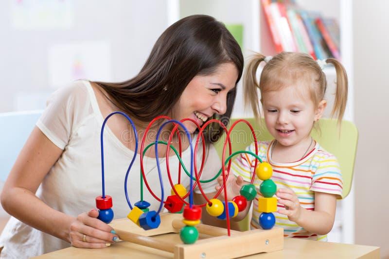 Fille heureuse et maman d'enfant jouant le jouet photos stock