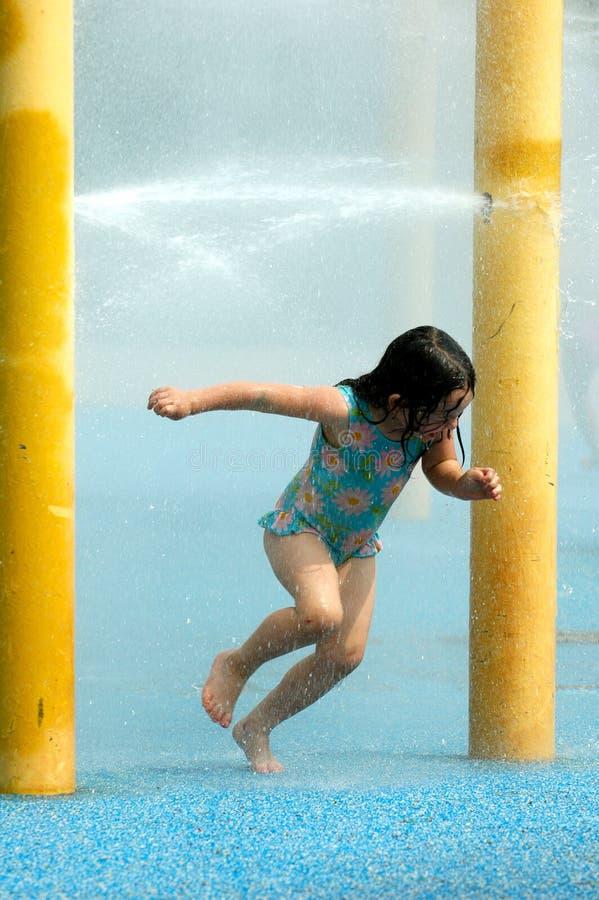 Fille heureuse jouant avec de l'eau photo stock
