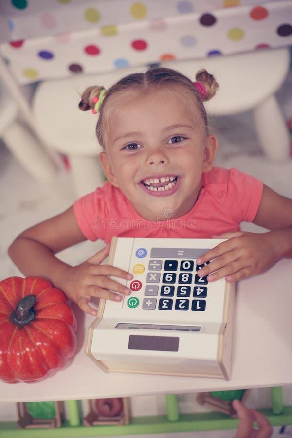 Fille heureuse jouant avec l'argent liquide d'enfants image libre de droits