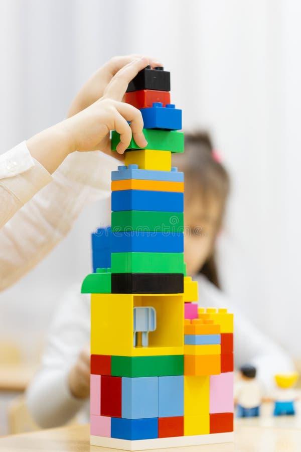 Fille heureuse jouant avec les blocs constitutifs colorés dans une salle de crèche photo libre de droits