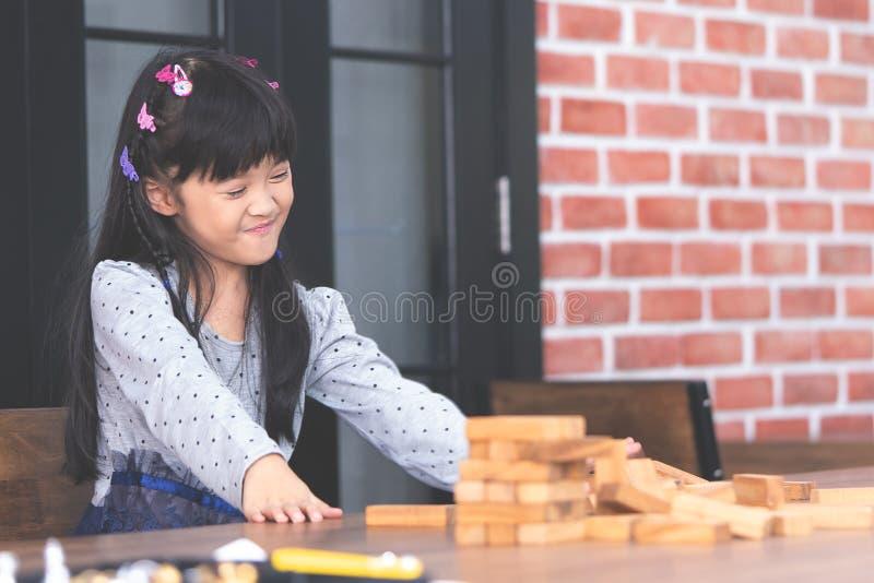 Fille heureuse jouant construisant un collapsi en bois de tour de bloc de jouet image stock