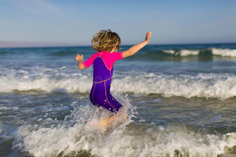 Fille heureuse jouant dans les vagues images stock