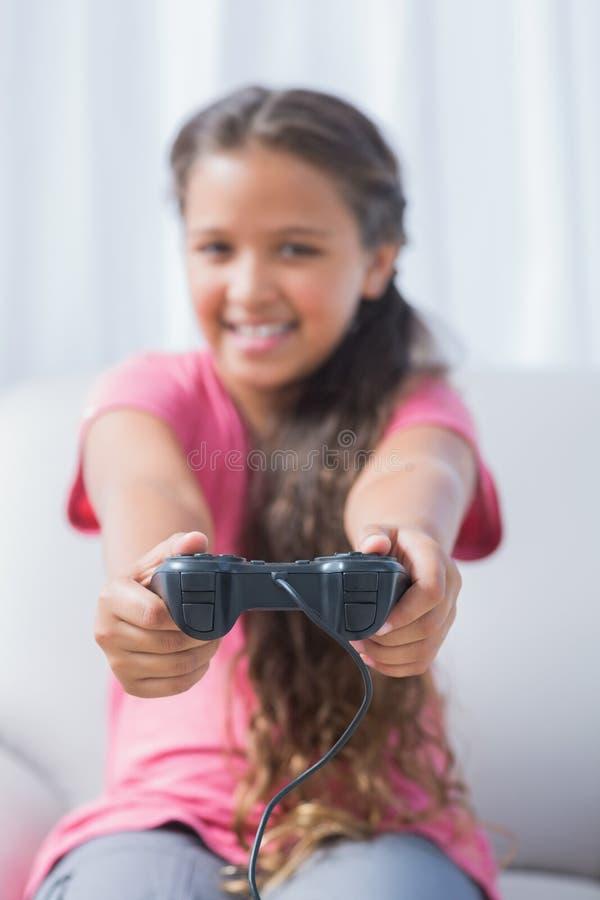 Fille heureuse jouant le jeu vidéo sur le sofa photos libres de droits