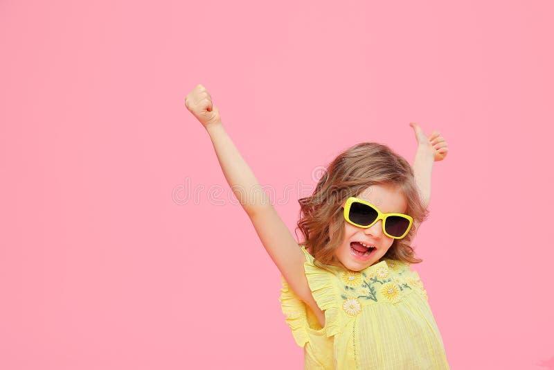 Fille heureuse merveilleuse expressive enthousiaste dans la robe et des lunettes de soleil jaunes image libre de droits